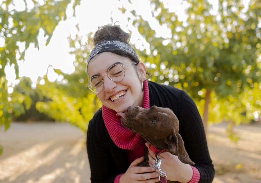 Portrait in a park of a teenage girl smiling while her dachshund licking her face